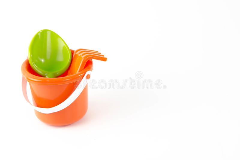 Summer toys bucket with spade isolated. Summer toys bucket for on the beach with spade isolated on white background royalty free stock photo