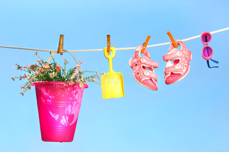 Summer toys and sandals on clothesline. Against a blue sky royalty free stock photos