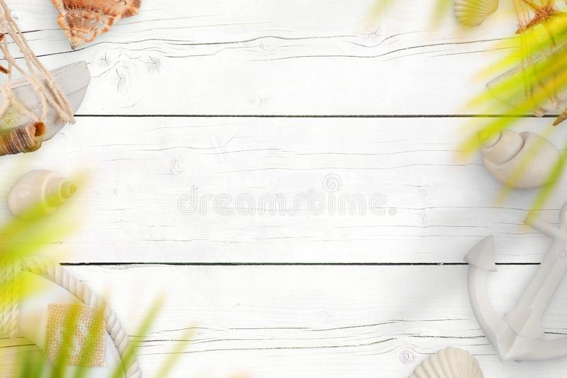 Summer travel background. White wooden desk with sea shells, boat anchor and life belt royalty free stock photos