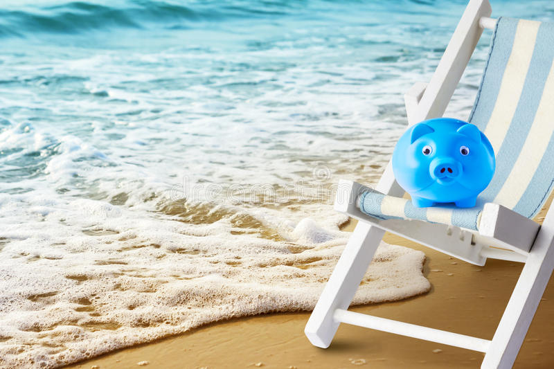 Summer and travel concept piggy bank on beach chair at beach royalty free stock photo