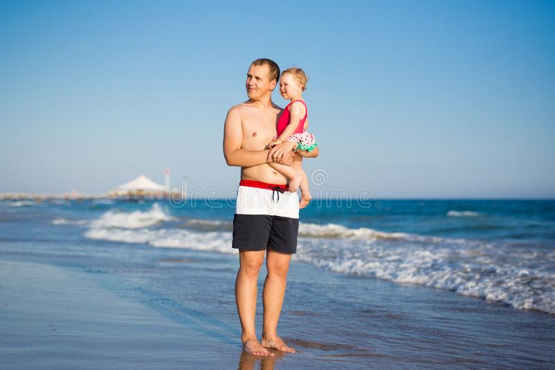Summer and travel concept - portrait of happy father with little daughter at the beach stock photos