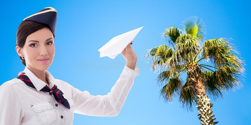 Summer and travel concept - pretty stewardess with paper plane over beach background royalty free stock image
