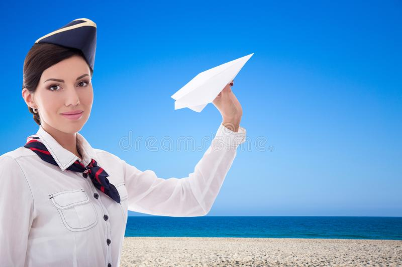 Summer and travel concept - stewardess with paper plane over beach background royalty free stock image