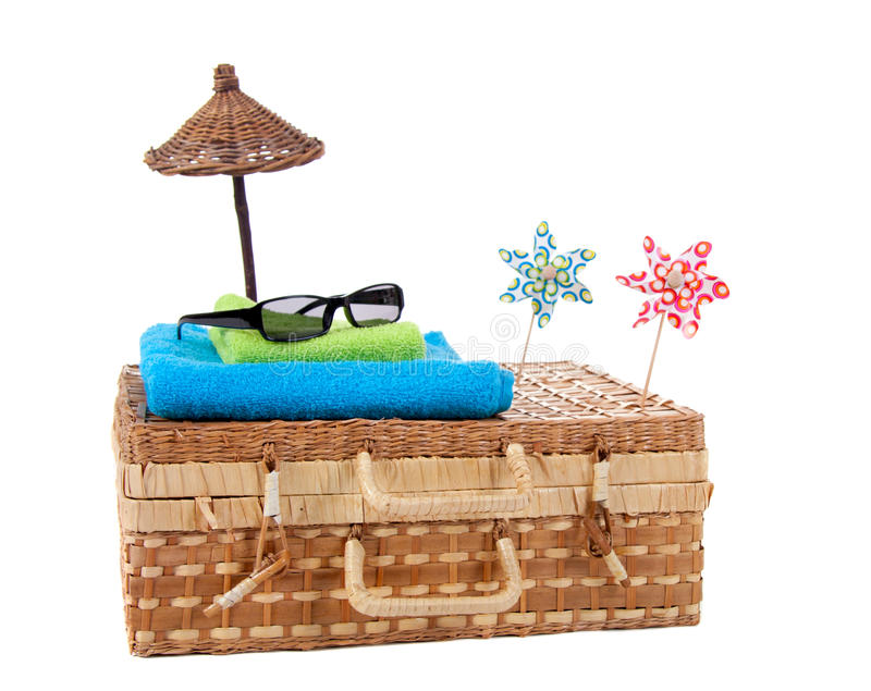 Summer travel equipment. Modern sunglasses on top of beach-towels on a wicker travel suitcase isolated over white stock images