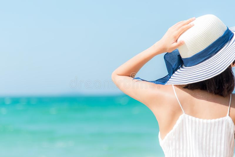 Summer Travel. Happy and Relax woman hand holding big hat on white sand beach,. Freedom lifestyle royalty free stock photography