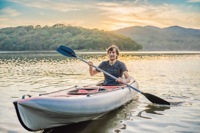 Summer Travel Kayaking Man die Transparante Canoe Kayak opzadelt, vrolijke recreatieve sportactiviteiten Male Canoeing stock afbeelding