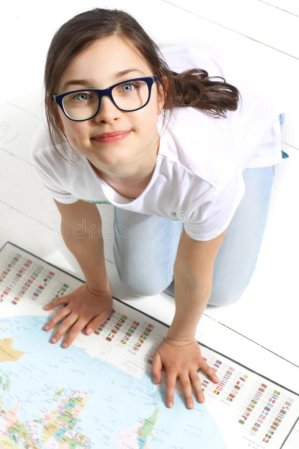Summer travel plan. The girl shows a finger on the world map the direction of the summer expedition royalty free stock images