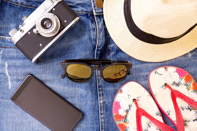 Summer travel set - camera, denim mini skirt, sandals, phone, sunglasses, hat stock images