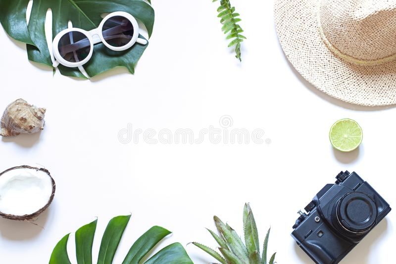 Summer travel tropical frame with a photo camera on the white background. Vacation concept flat lay. Top view. Copy space stock images