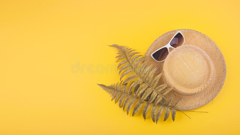 Summer travel vacation concept flat lay. Beach accessories, straw hat, golden tropical leaves and white sunglasses on yellow stock photos