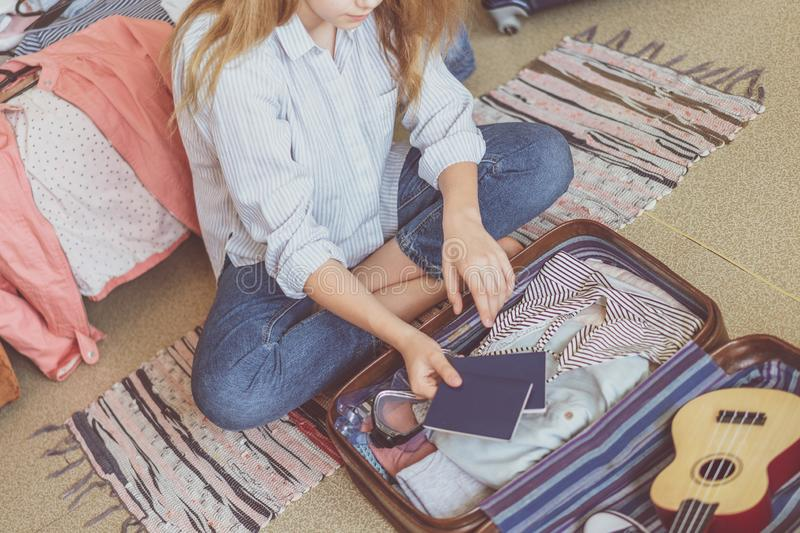 Summer travel and vacation concept. Young woman packing suitcase at home royalty free stock images