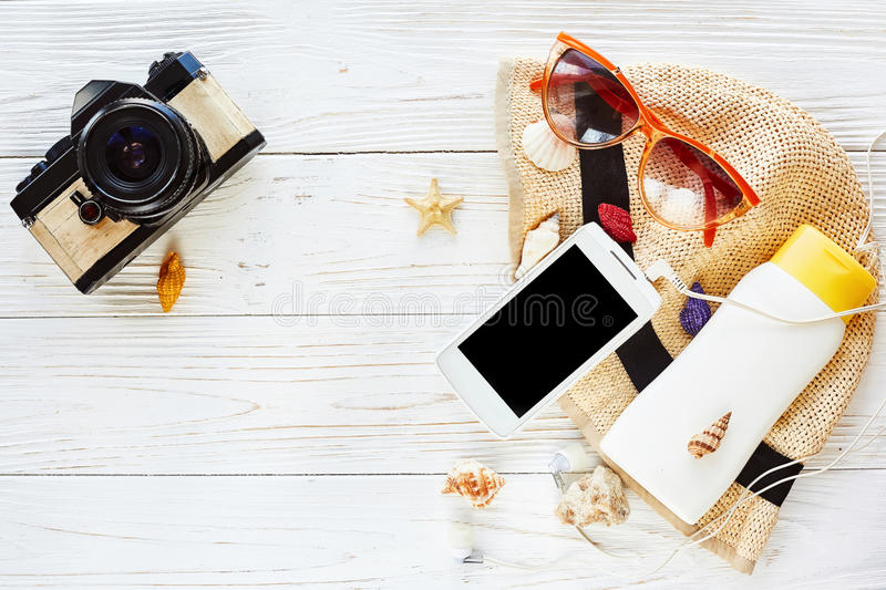 summer travel vacation flat lay concept. photo camera and hat sunscreen phone with empty screen and sunglasses on white wooden ba stock photos