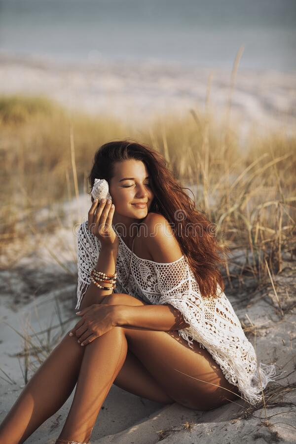 Woman With Seashell on the Beach During Vacations. Summer travel vacation relaxation concept. An attractive brunette woman with shell sitting on a sandy tropical stock photography