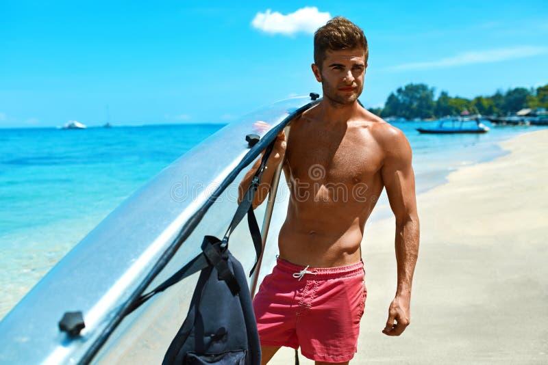 Summer Travel Water Sport. Man Holding Canoe Kayak On Beach. Summer Water Sport. Handsome Athletic Man With Body Holding Transparent Canoe Kayak. Beautiful Male stock photos