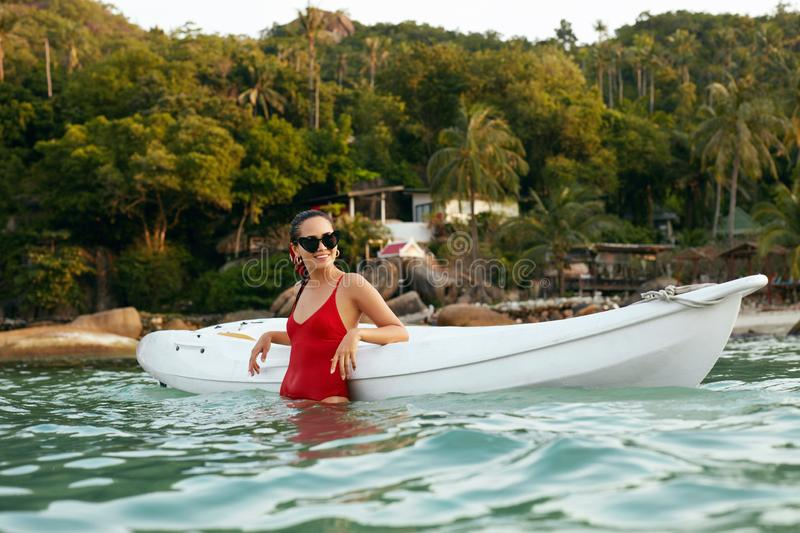 Summer Travel. Woman In Red Swimsuit Leaning On Kayak In Sea royalty free stock photo