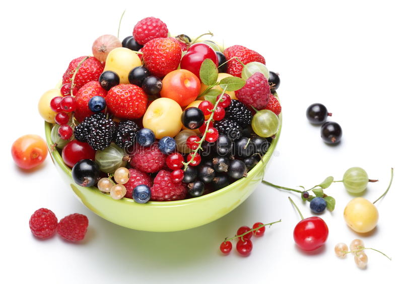 Summer treasure. Colourful ripe berries in the bowl on a white background royalty free stock photos