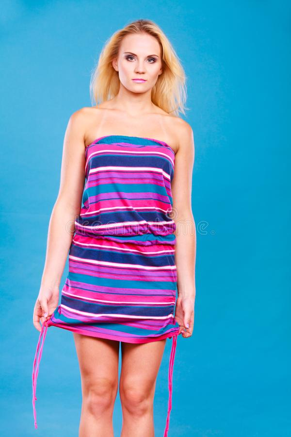 Blonde woman wearing short colorful striped dress royalty free stock image