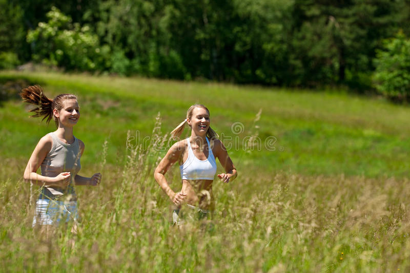 Summer - Two young woman jogging in a meadow stock photos