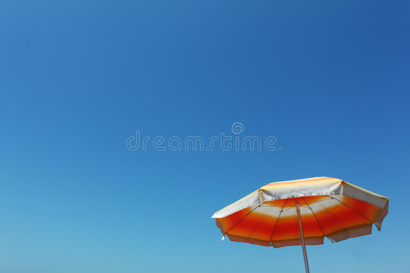 Summer umbrella. In clean blue sky royalty free stock photography