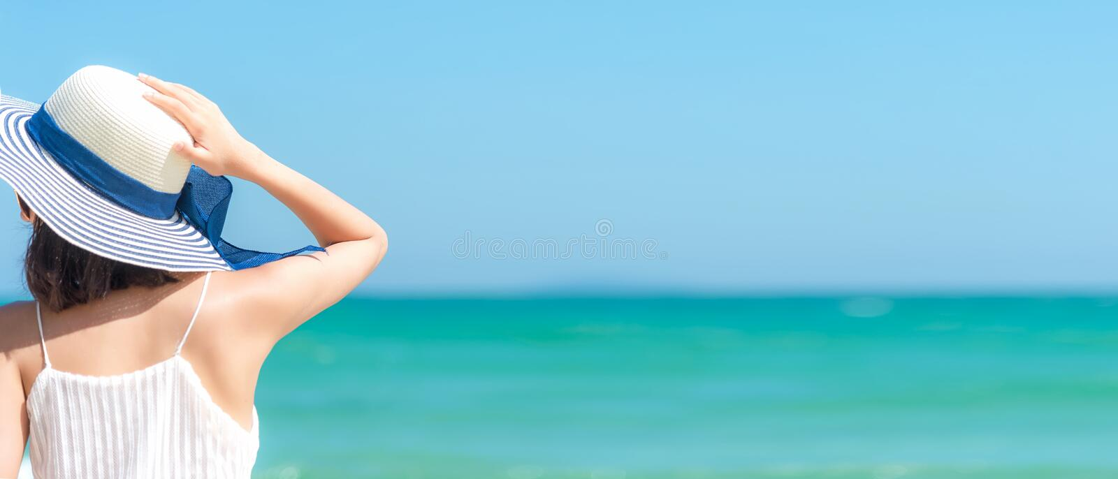 Summer Vacation. Asian women relaxing on the beach, so happy and luxury in holiday summer, blue sky background, copy space for tex stock photography