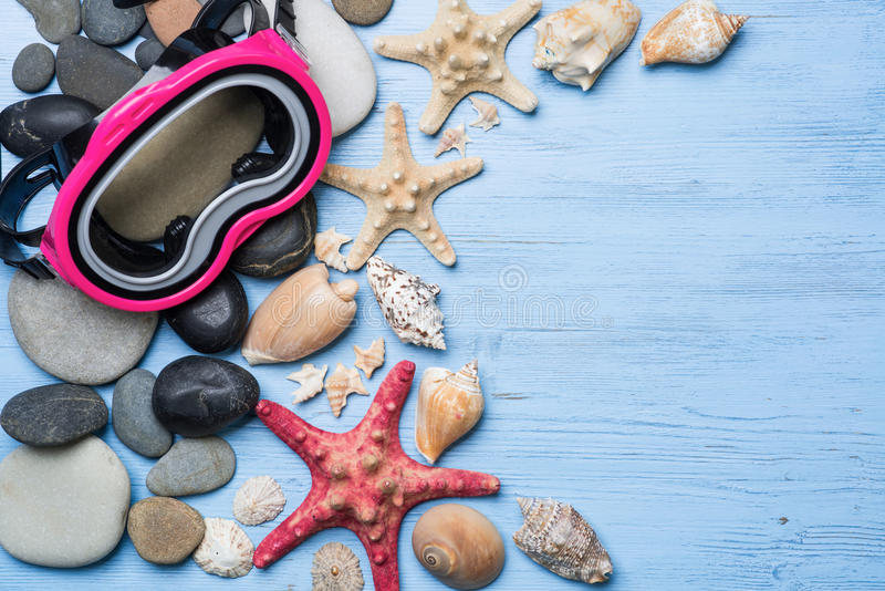 Summer vacation background. Diving mask with starfish and shells on blue wooden background royalty free stock image