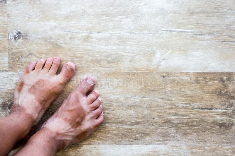 Male legs with suntanned shape of sandals and copy space on wooden floor. Summer vacation background - male legs with suntanned shape of sandals and copy space royalty free stock images