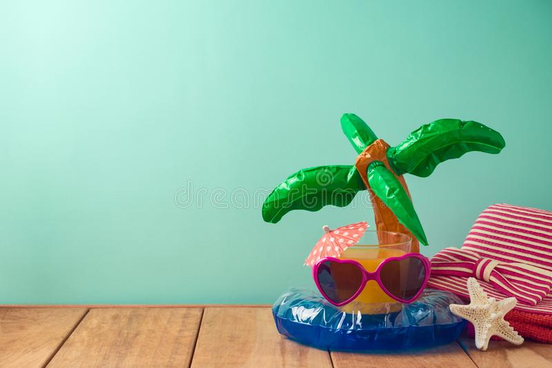 Summer vacation background with orange juice, beach accessories and pool float on wooden table. Summer vacation  background with orange juice, beach accessories royalty free stock photography
