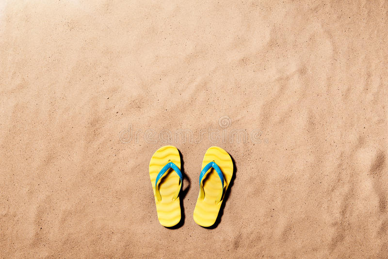 Summer vacation background with a pair of flip flop sandals. Summer vacation composition with a pair of yellow flip flop sandals on a beach. Sand background stock photo