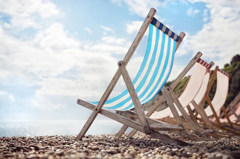 Summer vacation deck chairs on the beach at the seaside. Summer vacation beach deck chairs at the seaside stock images