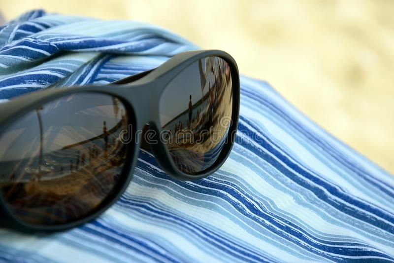 Summer vacation, beach holiday. Reflection in sunglasses - silhouettes of people sunbathing by sea, beach umbrellas and lounge stock photography