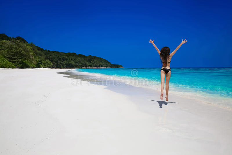 Summer vacation. Beautiful free woman jumping on the exotic sea. Over blue sky. Brunette bikini girl jumping on tropical beach with white sand. Enjoyment royalty free stock images