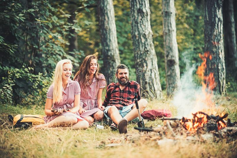 Summer vacation in camp. Bearded man and women smile at bonfire. Happy friends at campfire. Hipster in palid shirt and stock images