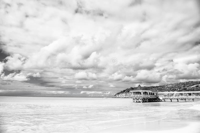 Summer vacation on caribbean. Sea beach with wooden shelter in antigua. Pier in turquoise water on cloudy sky background stock image