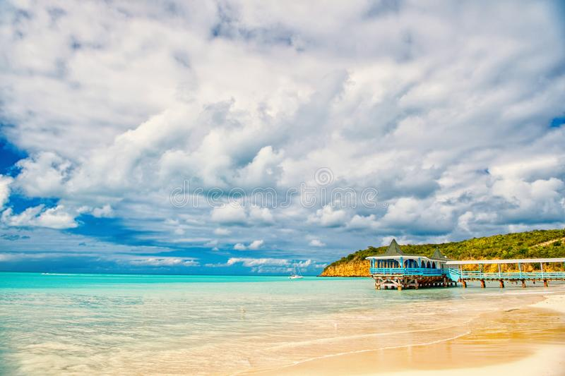 Summer vacation on caribbean. Sea beach with wooden shelter in antigua. Pier in turquoise water on cloudy sky background stock images