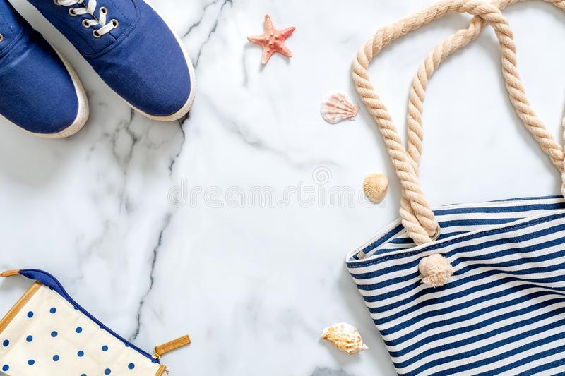 Summer vacation composition. Fashionable blue sneakers, striped beach bag, seashells, sea star on marble background. Women`s desk. Of traveller, beauty blogger stock photography