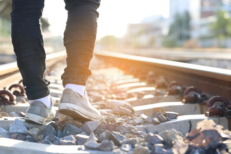 Summer vacation concept, Closeup of Man sneaker shoes walking at train station on evening sunset light.  stock photos