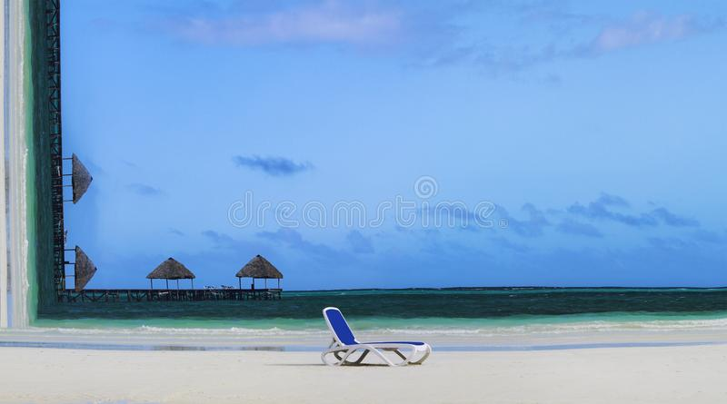 Summer vacation concept. Conceptual picture of tropical beach with lounge chair on sand and sun umbrellas on background. Tropical. Thatch umbrellas on a royalty free stock image