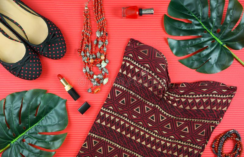 Summer vacation concept flatlay with summer dress and feminine accessories. Summer vacation concept flatlay with summer dress and feminine accessories on red stock images
