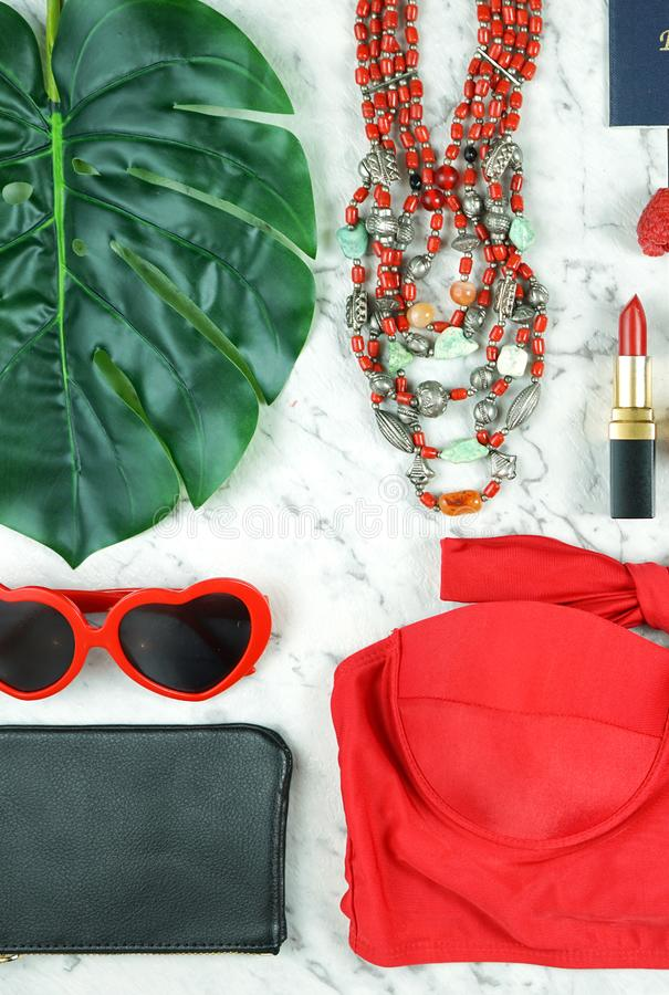 Summer vacation concept flatlay with red feminine accessories. Summer vacation concept flatlay with red feminine accessories on white marble background royalty free stock photo