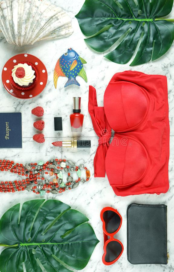 Summer vacation concept flatlay with red feminine accessories. Summer vacation concept flatlay with red feminine accessories on white marble background royalty free stock image