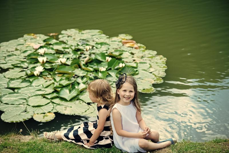 Summer vacation concept. Girls sit on grass at pond with water lily flowers. Children happy smile on green lake landscape. Future and flourishing. Germination royalty free stock photos