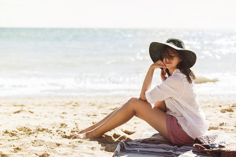 Summer vacation concept. Happy young woman relaxing on beach. Hipster slim girl in white shirt and hat sitting and tanning on. Beach near sea with waves, sunny stock images