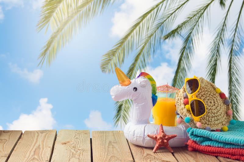 Summer vacation concept with orange juice, beach accessories. And unicorn pool float over sea beach background royalty free stock photography