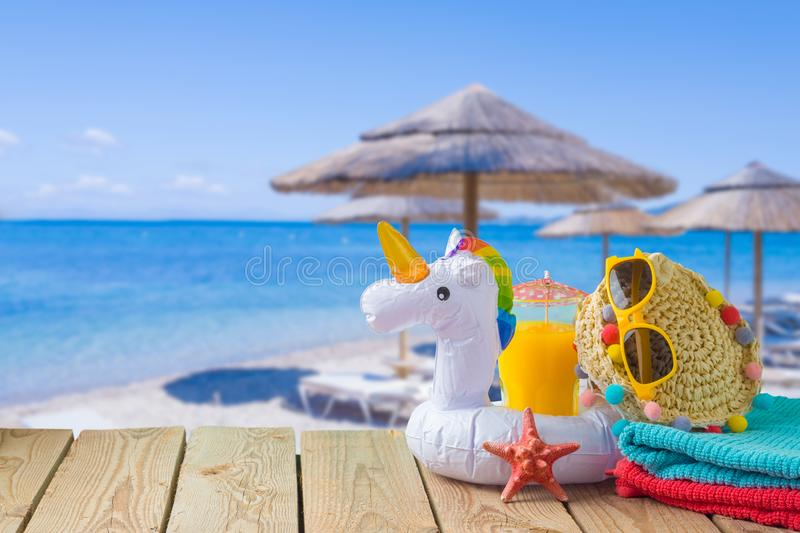 Summer vacation concept with orange juice, beach accessories and unicorn pool float over sea beach background. Summer vacation concept with orange juice, beach royalty free stock images