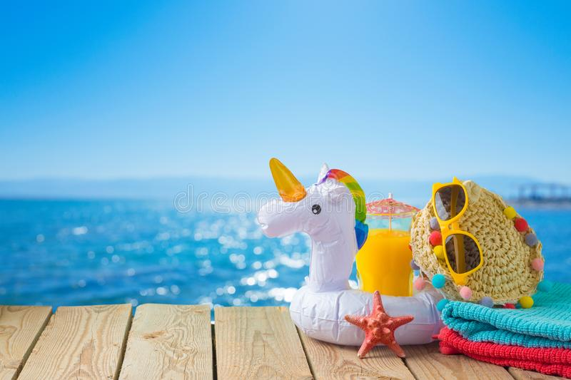 Summer vacation concept with orange juice, beach accessories and unicorn pool float over sea beach background. Summer vacation concept with orange juice, beach stock photo