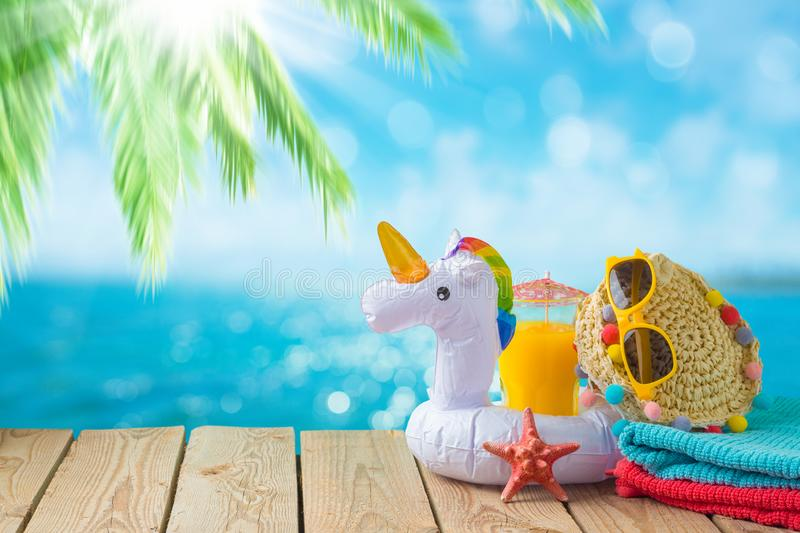 Summer vacation concept with orange juice, beach accessories and unicorn pool float over sea beach background. Summer vacation concept with orange juice, beach royalty free stock image