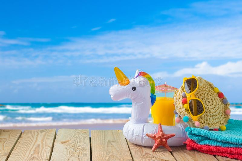 Summer vacation concept with orange juice, beach accessories and unicorn pool float over sea beach background. Summer vacation concept with orange juice, beach stock photos