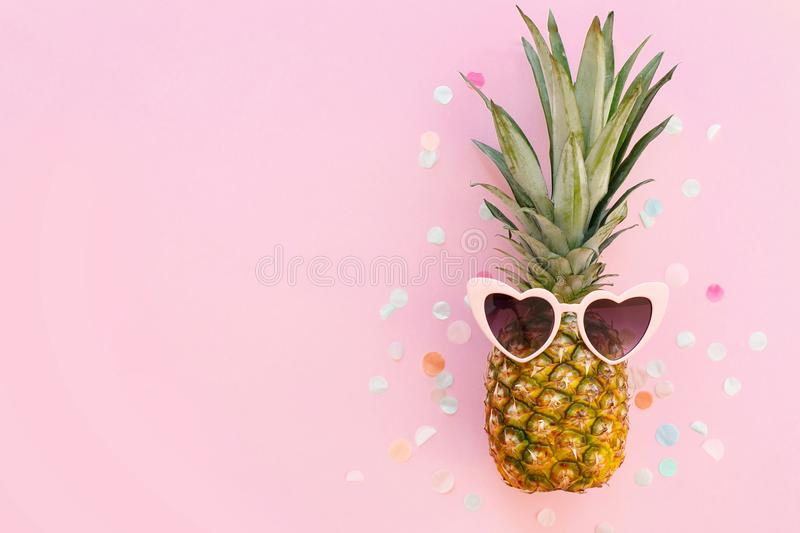 Summer vacation concept. pineapple in pink sunglasses on trendy. Pink paper background with confetti. minimalism flat lay. party concept. space for text. summer stock photo