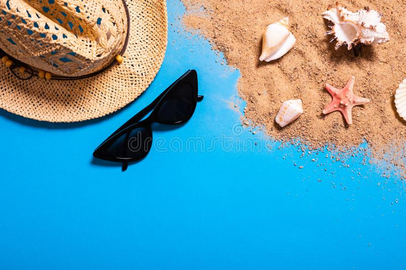 Summer vacation concept with seashells, starfish, women`s beach hat and sunglasses on a blue background and sand. stock photography