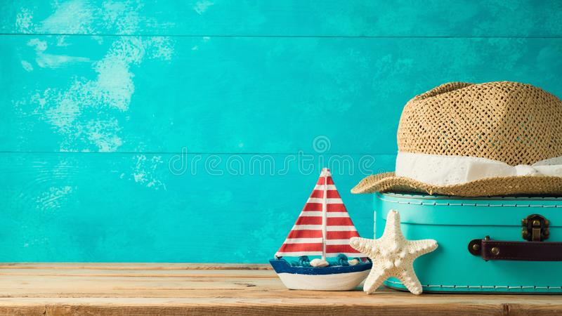 Summer vacation concept. Suitcase box, hat and boat decor over wooden background. Summer vacation concept royalty free stock photos